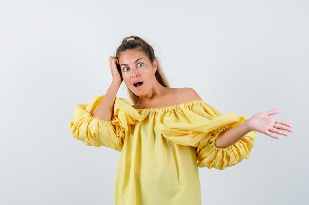Ritratto di giovane donna che mostra qualcosa, tenendo la mano sulla testa in abito giallo e guardando stupito vista frontale