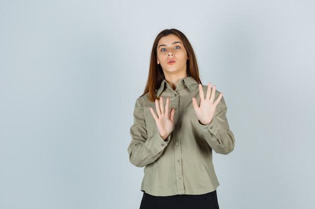 Ritratto di giovane donna che mostra il gesto di arresto in camicia, gonna e sembra spaventata vista frontale