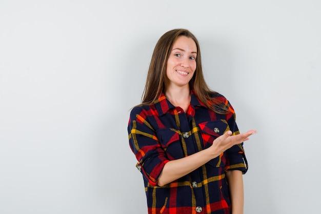 Ritratto di giovane donna che mostra gesto di benvenuto in camicia casual e guardando vista frontale allegra