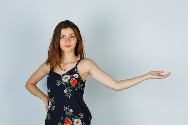 Portrait of young lady spreading her arm in floral top and looking pleased