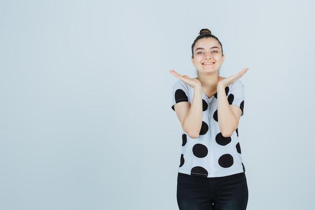 Ritratto di giovane donna allargando le palme in t-shirt, jeans e guardando carino vista frontale