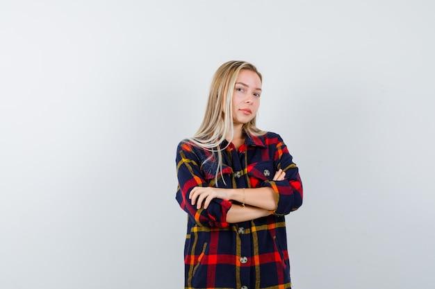 Ritratto di giovane donna in piedi con le braccia incrociate in camicia a quadri e guardando fiducioso vista frontale