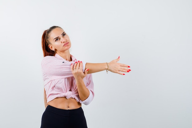 Portrait of young lady stretching arms in shirt, pants and looking relaxed front view