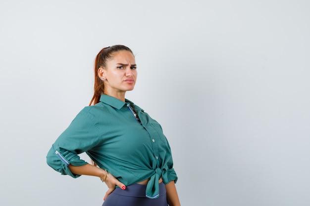 Ritratto di giovane donna che soffre di mal di schiena in camicia verde e sembra una vista frontale scomoda