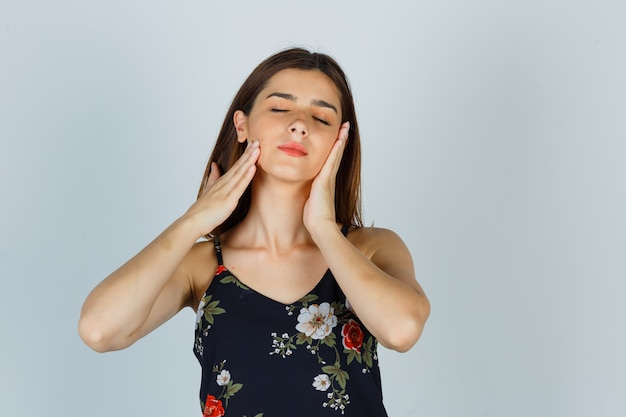 Ritratto di giovane donna che tocca la pelle del viso sulle guance in camicetta e sembra una vista frontale rilassata