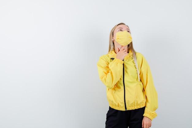 Ritratto di giovane donna che tocca il suo collo mentre cerca in tuta da ginnastica, maschera e vista frontale da sogno
