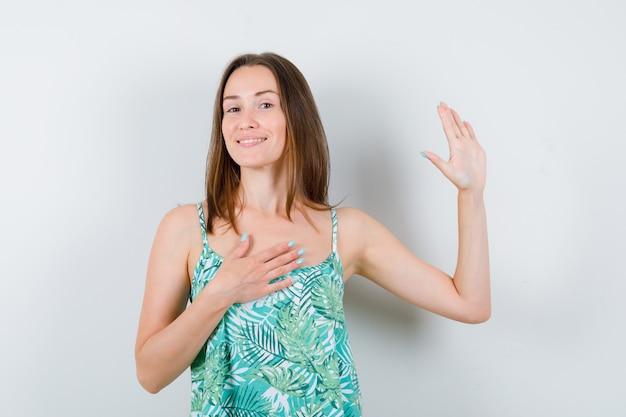 Ritratto di giovane donna agitando la mano per salutare in camicetta e guardando allegra vista frontale