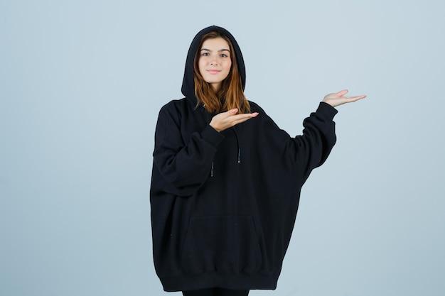 Ritratto di giovane donna accogliente in felpa con cappuccio oversize, pantaloni e guardando felice vista frontale