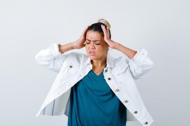 Ritratto di giovane donna con le mani sulla testa in giacca bianca e guardando stanco vista frontale