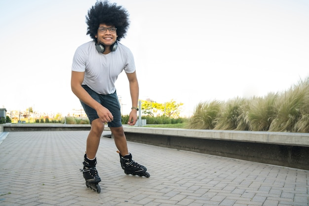 Portrait of young latin man rollerskating outdoors on the street