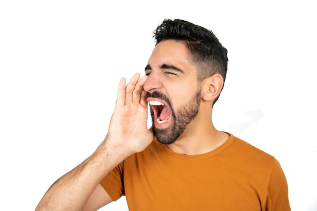 Ritratto di giovane uomo latino che grida e urla contro lo spazio bianco