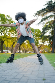 Portrait of young latin man wearing face mask while roller skating outdoors on the street