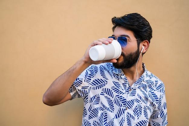 Ritratto di giovane uomo latino che indossa abiti estivi, bere una tazza di caffè e ascoltare musica con gli auricolari contro lo spazio giallo.
