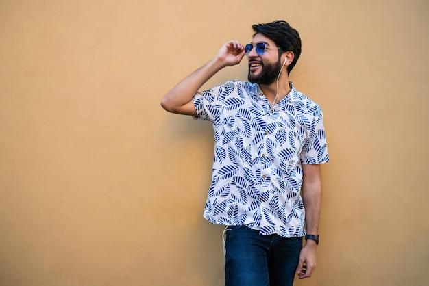 Ritratto di giovane uomo latino che indossa abiti estivi e ascolto di musica con gli auricolari contro lo spazio giallo.