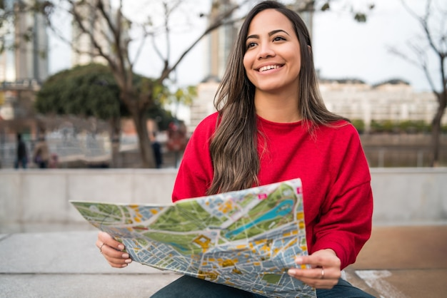 Portrait of young latin woman holding a map and looking for directions outdoors in the street. travel concept.
