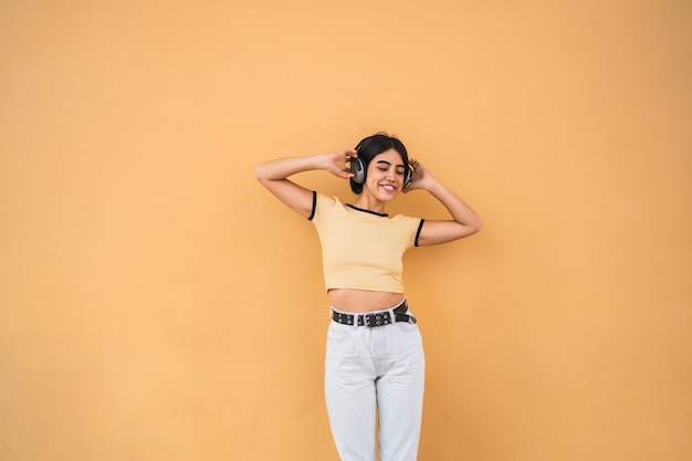 Portrait of young latin woman listening to music with headphones against yellow space. urban concept.