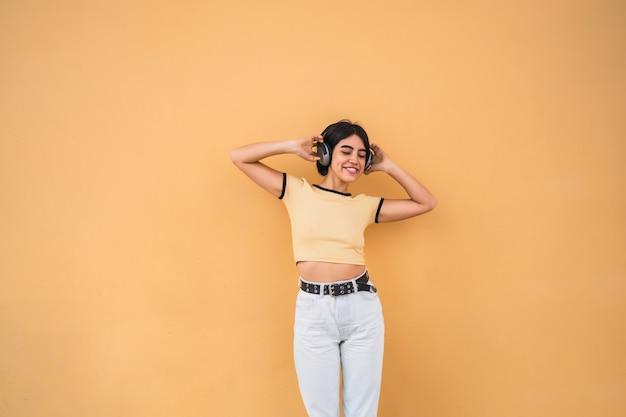Ritratto di giovane donna latina che ascolta la musica con le cuffie contro lo spazio giallo. concetto urbano.
