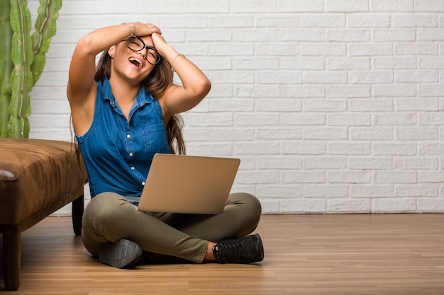 Portrait of young latin woman sitting on the floor frustrated and desperate, angry and sad with hands on head