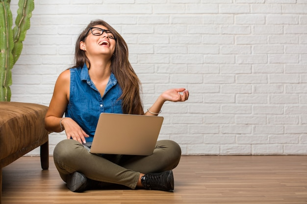 Portrait of young latin woman sitting on the floor laughing and having fun, being relaxed and cheerful