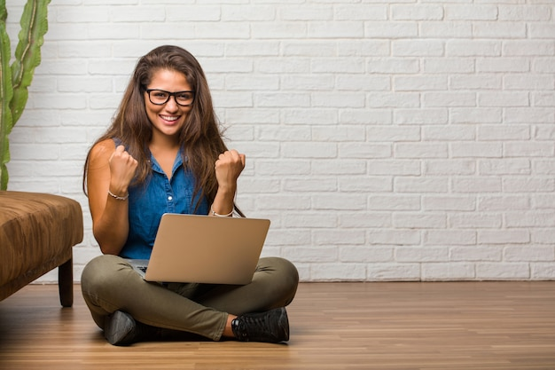 Portrait of young latin woman sitting on the floor very happy and excited, raising arms