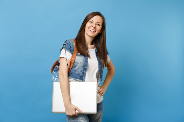 Portrait of young laughing happy woman student in white t-shirt denim clothes with backpack hold laptop pc computer isolated on blue background. education in high school. copy space for advertisement.