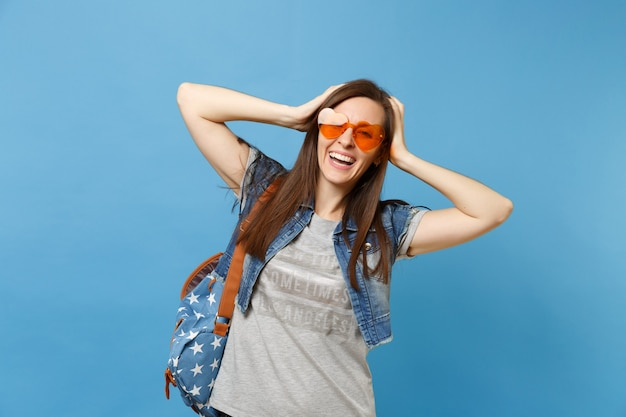 Portrait of young laughing joyful beautiful woman student with backpack in orange heart glasses clinging to head isolated on blue background. education in high school. copy space for advertisement.