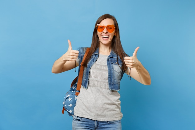 Portrait of young laughing pretty funny woman student with backpack wearing orange heart glasses showing thumbs up isolated on blue background. education in university. copy space for advertisement.