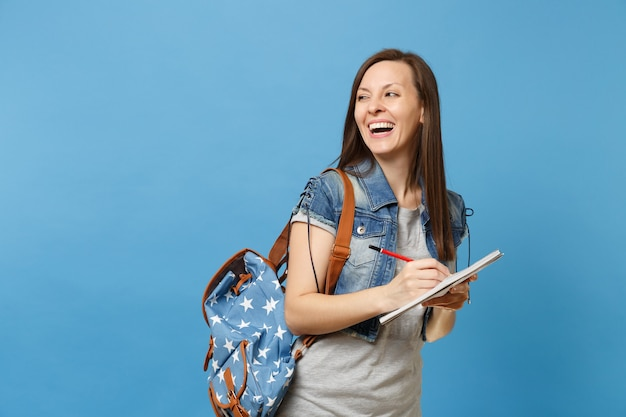 Portrait of young laughing woman student in denim clothes with backpack looking aside on copy space writing notes on notebook isolated on blue background. education in high school university college.