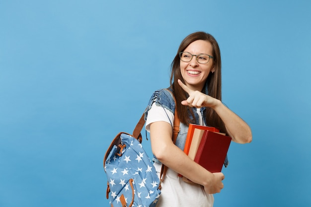 Portrait of young laughing woman student in glasses with backpack holding books, pointing index finger away look aside isolated on blue background. education in high school university college concept.