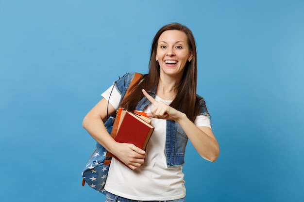 Portrait of young laughing woman student with backpack pointing index finger aside on copy space, holding school books isolated on blue background. education in high school university college concept.