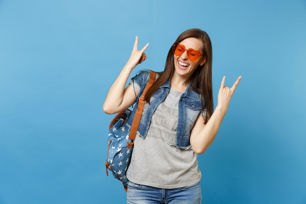 Portrait of young laughing woman student with closed eyes with backpack in orange heart glasses show rock-n-roll sign isolated on blue background. education in college. copy space for advertisement.