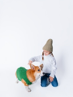 Portrait of young little girl with her pet puppy of corgi.