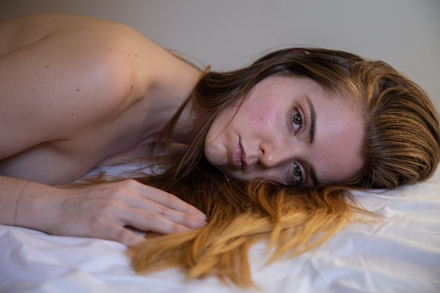 Portrait of young lonely pretty woman with brown hair lying on bed and looking