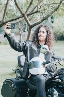 Portrait of a young long hair man, an old biker in a leather jacket on a retro bike, vintage classic motorcycle. concept of freedom and style, a hobby for life. copy space, takes selfie