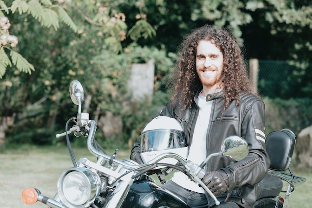 Portrait of a young long hair man, an old biker in a leather jacket on a retro bike, vintage classic motorcycle. concept of freedom and style, a hobby for life. copy space