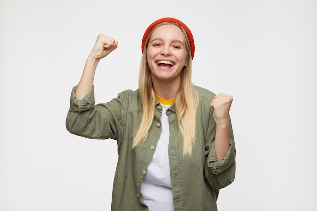 Portrait of young long haired blonde lady raising happily fists and looking joyfully, wearing red hat, olive shirt and white t-shirt while standing on blue