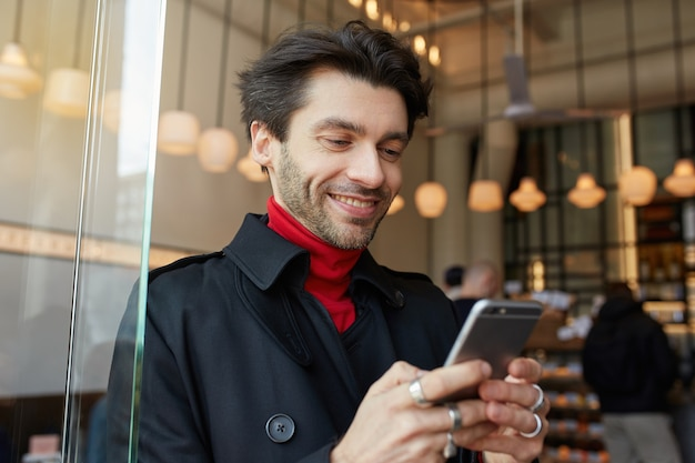 Portrait of young lovely brown haired unshaved male looking happily on screen of his phone and smiling cheerfully while standing over city cafe interior in trendy clothes