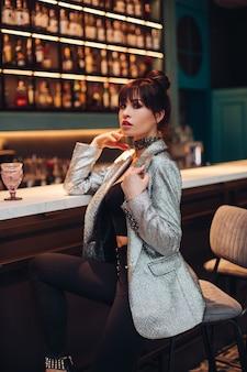 Il ritratto di giovane donna caucasica adorabile con capelli scuri in giacca d'argento, jeans neri e scarpe posa per la macchina fotografica