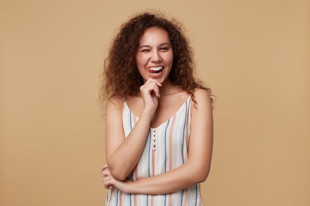 Ritratto di giovane donna castana riccia adorabile che fa l'occhiolino e mostra allegramente la lingua, tenendo la mano alzata mentre posa sul beige