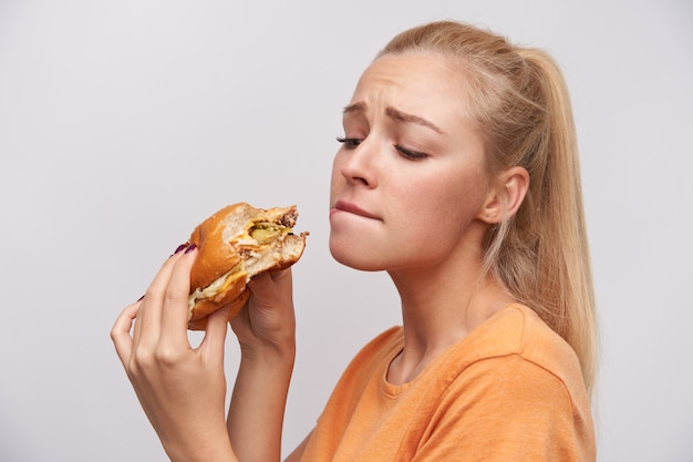 Portrait of young lovely long haired blonde female with ponytail hairstyle keeping burger in raised hands and looking insatiably on it, biting underlip and frowning eyebrows over white background