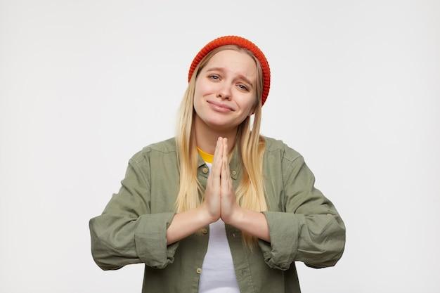 Ritratto di giovane bella donna bionda dai capelli lunghi mantenendo le palme sollevate insieme mentre elemosina qualcosa e sembra triste, posa sul blu