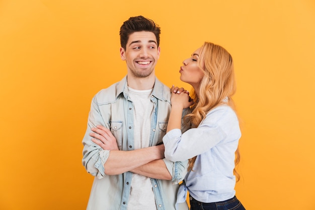 Portrait of young lovely people in basic clothing expressing love and affection while woman kissing man on cheek, isolated over yellow wall