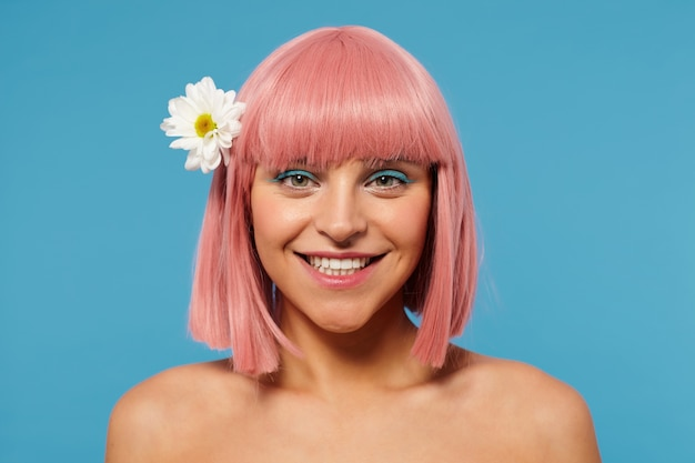 Portrait of young lovely positive pink haired female with short haircut looking happily at camera with charming smile, having chamomile in her hair while standing over blue background