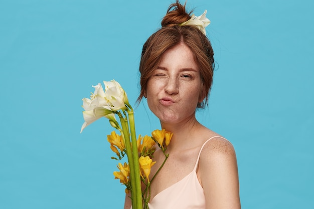 Portrait of young lovely redhead woman with natural makeup keeping one eye closed and pursing her lips while looking at camera, posing over blue background with flowers