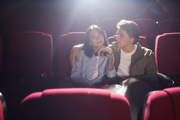 Portrait of young loving couple in cinema watching movie while enjoying date, man looking at girlfriend with affection and embracing her, copy space