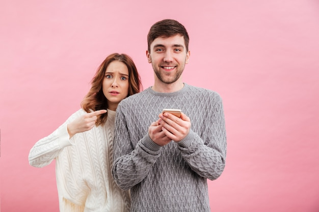 Portrait of young loving couple dressed in sweaters standing