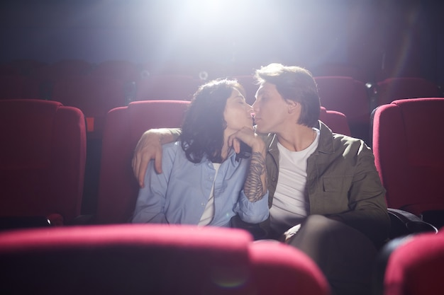 Portrait of young loving couple kissing in cinema while enjoying date, man embracing girlfriend in dark hall, copy space