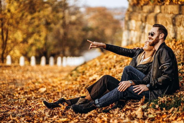Portrait of a young loving couple, sitting in autumn leaf and enjoying nature. the girl points a finger in the distance. love story