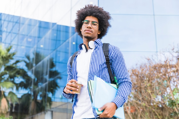 Portrait of a young male afro american student carrying bag on shoulder and books in hand standing against university building