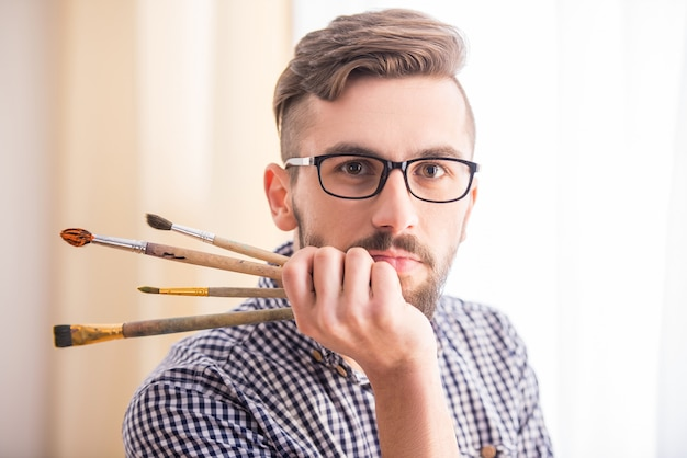 Portrait of a young male artist with brushes for painting.